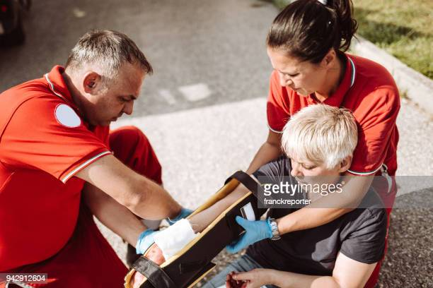 woman injured sitting in the ground after a car accident - bloody car accidents stock pictures, royalty-free photos & images