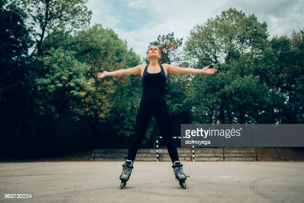 woman inline skates outdoors on a sunny day - inline skate stock photos and pictures
