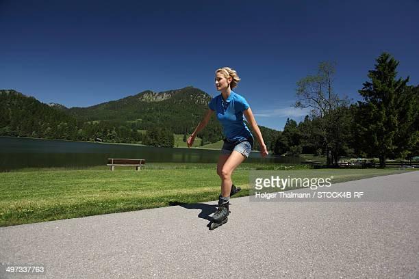 Woman inline skating at Spitzingsee, Bavaria, Germany