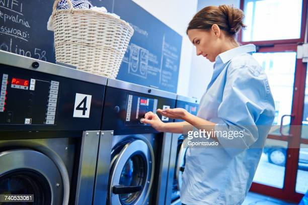 woman inserting coins into washing machine at laundrette - inserting stock pictures, royalty-free photos & images
