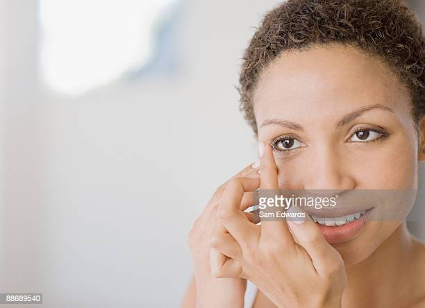 woman inserting contact lens - contacts stock photos and pictures