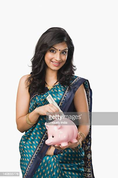 Woman inserting money into a piggybank