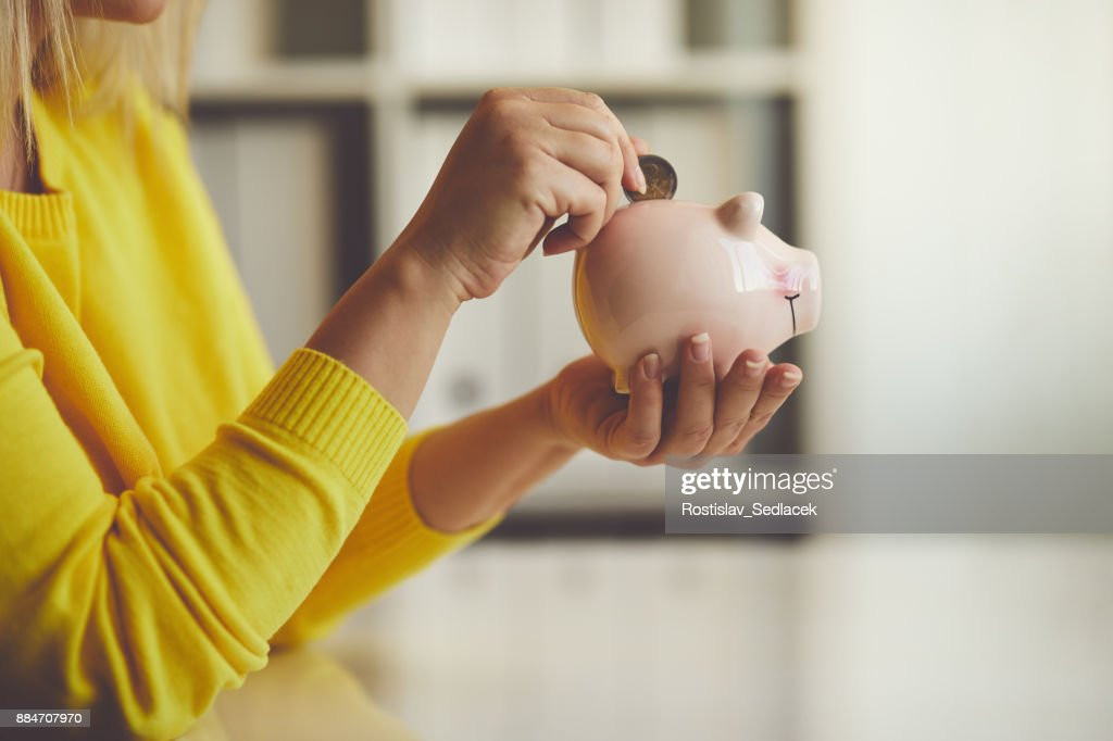 Woman inserts a coin into a piggy bank : Stock Photo