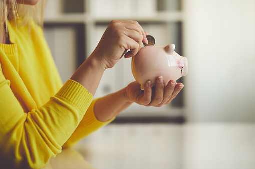 Woman inserts a coin into a piggy bank 884707970