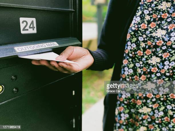 woman inserts envelope into outgoing mail slot - midterm election stock pictures, royalty-free photos & images
