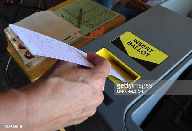 A woman inserts her ballot into the machine after voting at a Lifeguard headquarters that doubles as a polling station during the midterm elections...