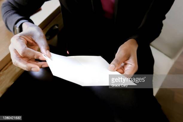woman inserts letter into envelope - responder imagens e fotografias de stock