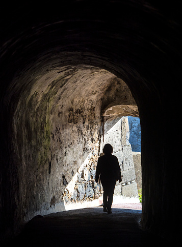 Woman inside a dark underground tunnel walking into the light.  Terceira Island in the Azores, Portugal. - gettyimageskorea