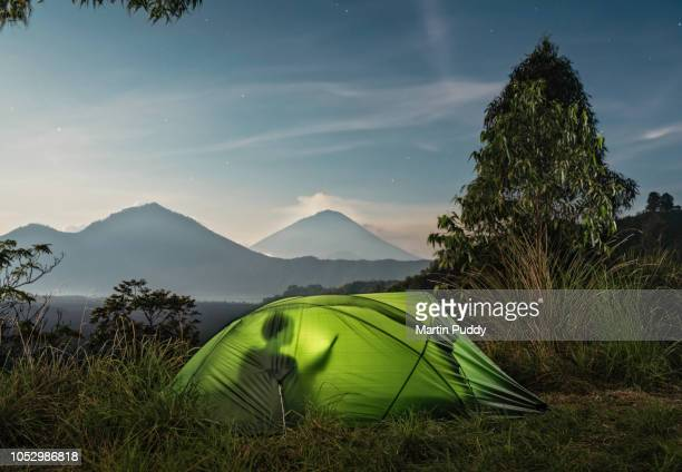 woman inside tent using digital tablet, under moonlight, in front of mount agung