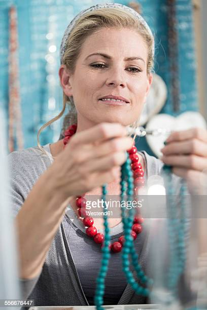 Woman inspecting a bead necklace