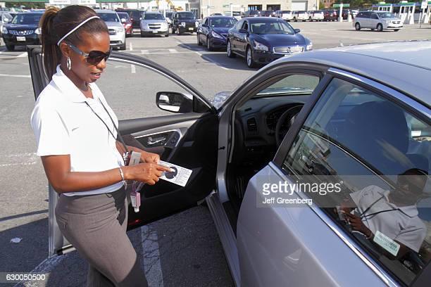 A woman inspecting a car for damage at Alamo car rental
