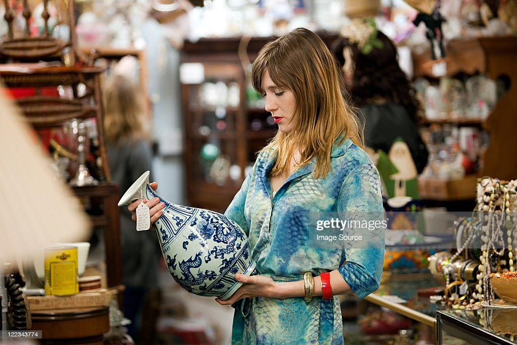 Woman inspecting vase in antiques shop : Stock-Foto