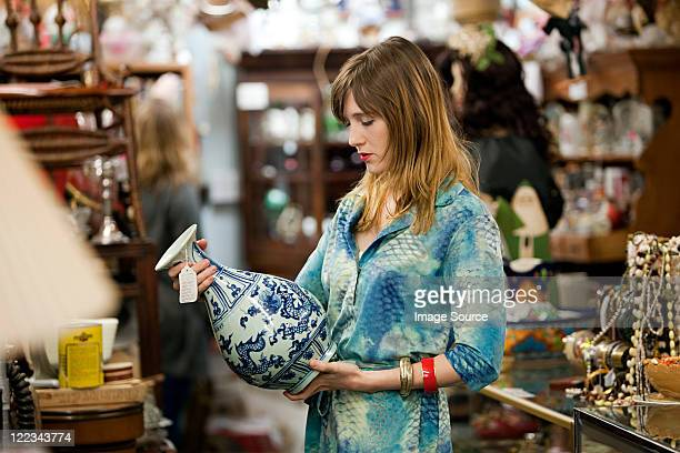 woman inspecting vase in antiques shop - antique stock pictures, royalty-free photos & images