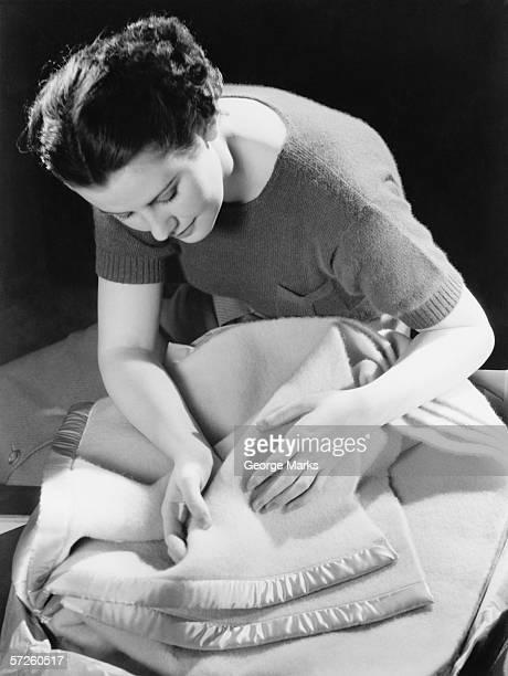 Woman inspecting woollen blanket, (B&W)
