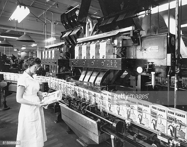 A woman inspects a Corn Flakes cereal box along the conveyor belt at the Corn Flakes division of Kellogg's main packaging plant
