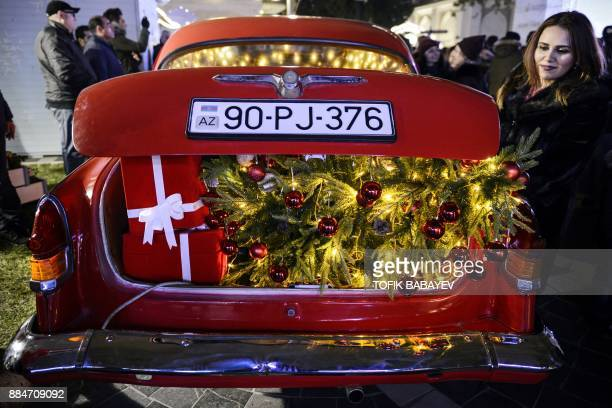 A woman inspects a decorated old car at the Christmas charity fair 'Cold Hands Hot Hearts' on the eve of Christmas and New Year in the center of Baku...