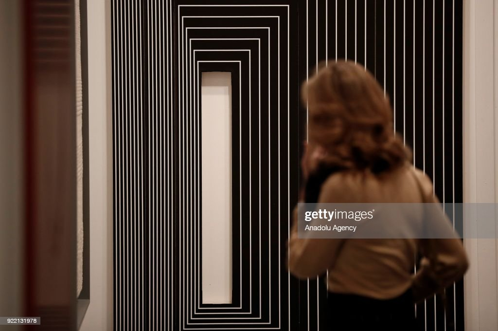 A woman inspects artworks during ARCOmadrid 2018 in Madrid, Spain on February 21, 2018.