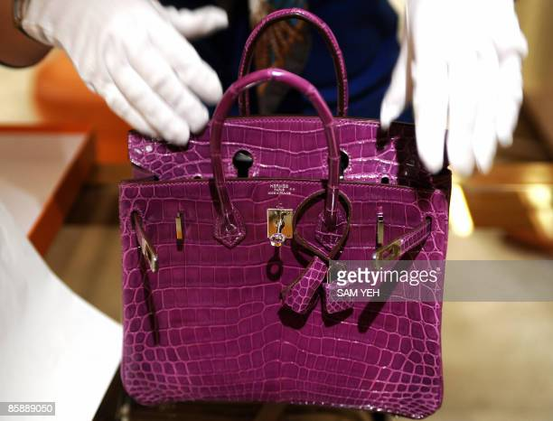 Woman inspects Hermes crocodile skin bag in Taipei on April 10, 2009. French luxury goods group Hermes hailed a Taiwan court's ruling to impose a...
