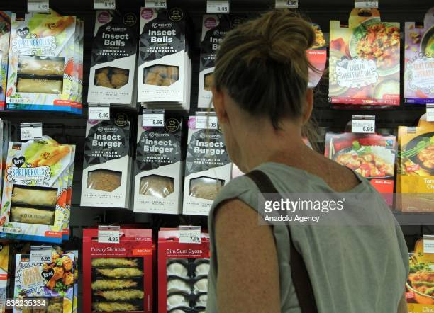 A woman inspects Insect Burgers which are seen on sale in Switzerland's second biggest supermarket chain in Geneva Switzerland on August 21 2017...