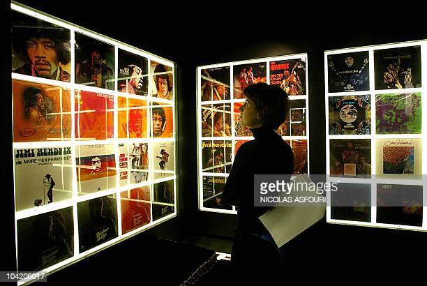 A woman inspects Jimi Hendrix record covers on display at the Marquee club in London 16 September 2004 The Jimi Hendrix Experience exhibition for the...
