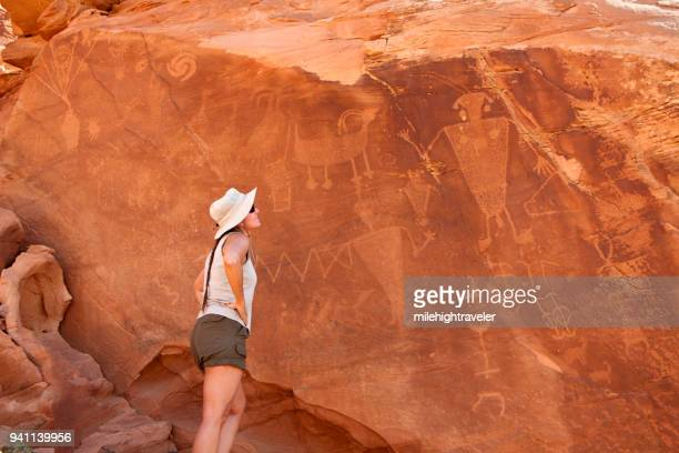 Woman inspects Native American Fremont Indian Dinosaur National Monument petroglyphs Utah