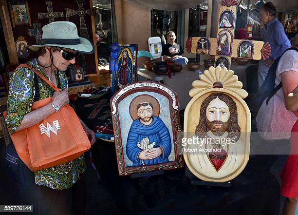 Woman inspects painted wooden relief panels by Hispanic artist Ronald Martinez at the Spanish Market on July 30, 2016 in Santa Fe, New Mexico. The...