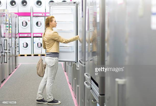 Woman inspects refrigerator space inside appliance store
