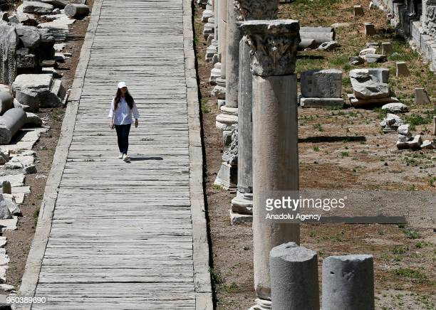 A woman inspects the Ancient Ephesus City Ruins which was used as a settlement for 9000 years and take place in World Heritage List of UNESCO World...