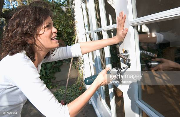 Woman installing lock on door