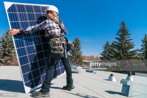 woman installing solar panels - powerofforever stock pictures, royalty-free photos & images