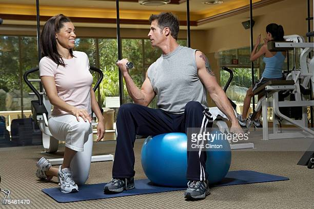 Woman instructor looking at man lifting weights