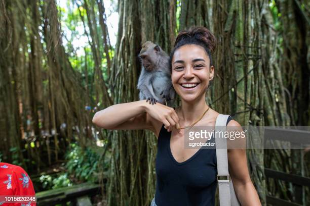 woman interacting with a monkey in bali, indonesia - wildlife reserve stock pictures, royalty-free photos & images