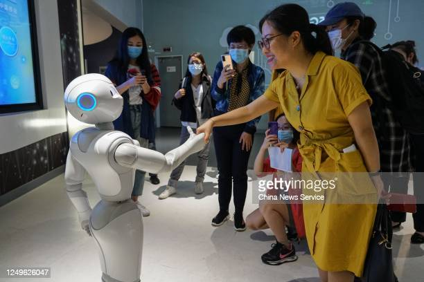 Woman interacts with a robot at a display center of the National Big Data Comprehensive Pilot Area on June 13, 2020 in Guiyang, Guizhou Province of...