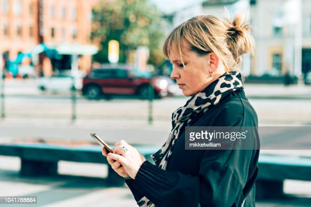 Woman interacts with her phone while walking outside in the city