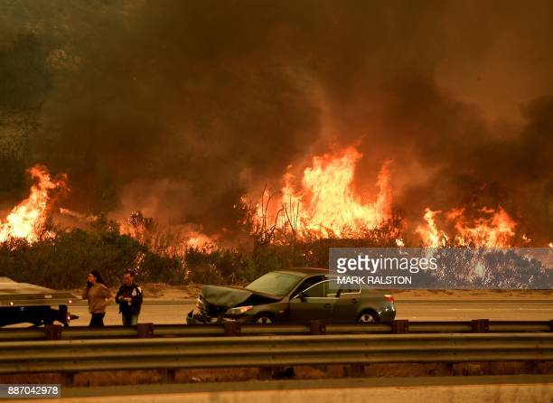 A woman involved in a traffic accident waits to get towed beside a wall of flames on the 101 highway during the Thomas wildfire near Ventura...
