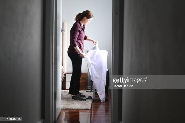 woman ironing clothes at home - rafael ben ari 個照片及圖片檔