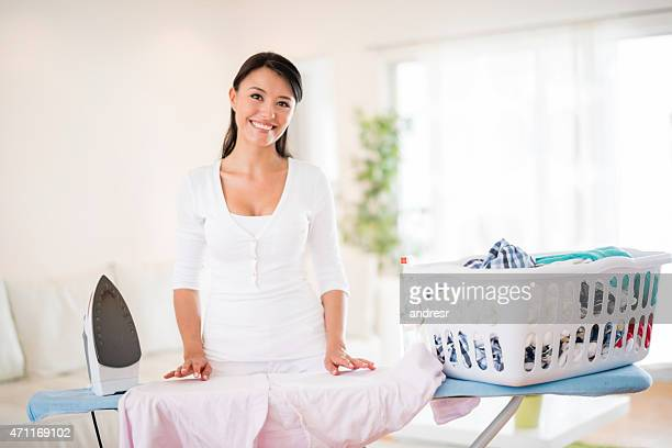Woman ironing clothes at home