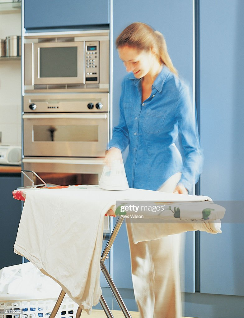 Woman Ironing Her Laundry In The Kitchen Stock Photo | Getty Images