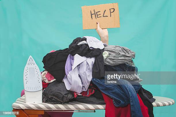 Woman ironing, hidden by large pile of laundry
