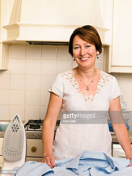 Woman ironing in her kitchen