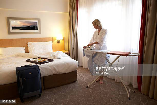 Woman ironing in hotel room