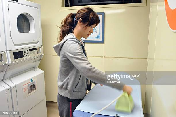 Woman ironing in public laundry room