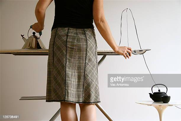 Woman ironing with tea kettle