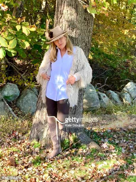 woman is a cowboy hat leaning against a tree - ブーツイン ストックフォトと画像