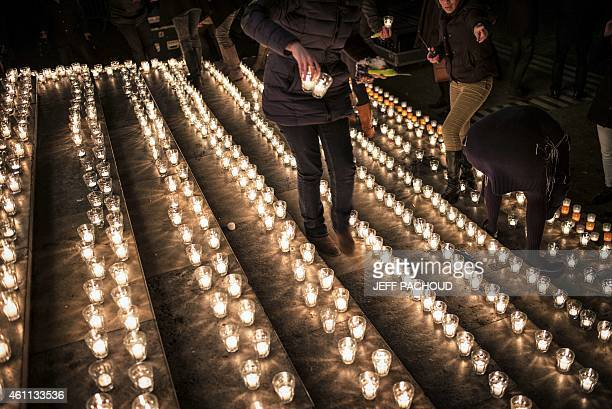 A woman is about to lay candles during a gathering in Lyon central eastern France on January 7 following an attack by unknown gunmen on the offices...