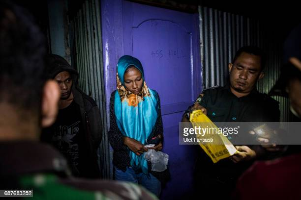 A woman is arrested by members of the sharia police known as Wilayatul Hisbah and Indonesian police for being outside at midnight which goes against...