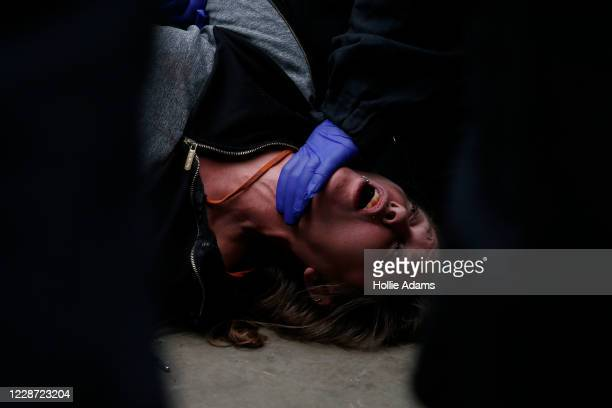 A woman is arrested by police officers during a We Do Not Consent antilockdown rally at Trafalgar Square on September 26 2020 in London England...