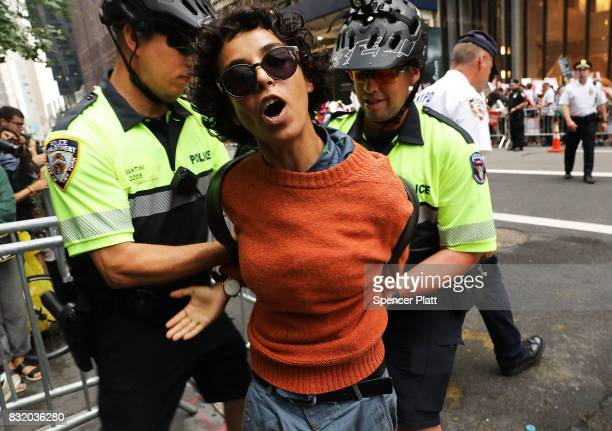 A woman is arrested during a pro immigration rally outside of Trump Tower along Fifth Avenue on August 15 2017 in New York City Security throughout...