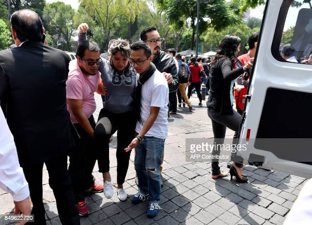 A woman is assisted after a real quake rattled Mexico City on September 19 2017 moments after an earthquake drill was held in the capital A 71...
