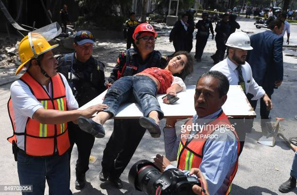 TOPSHOT A woman is assisted after being injured during a quake in Mexico City on September 19 2017 A powerful earthquake shook Mexico City on Tuesday...